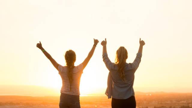 To stærke kvinder, som står med hænderne over hovedet ved en solopgang