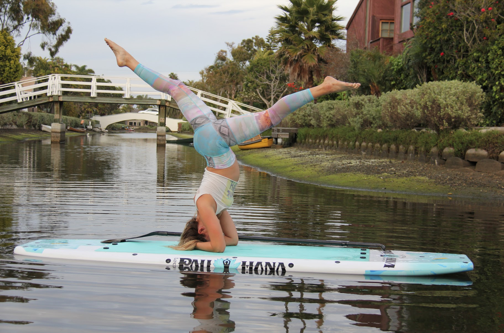 Yoga class with the Pau Hana Lotus Boards on the water doing a headstand