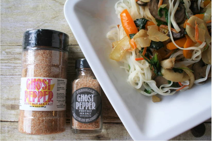 A large and sample size bottle of FreshJax Organic Ghost Pepper Hot sea salt on a table next to a bowl of Spicy Noodle Stir Fry.