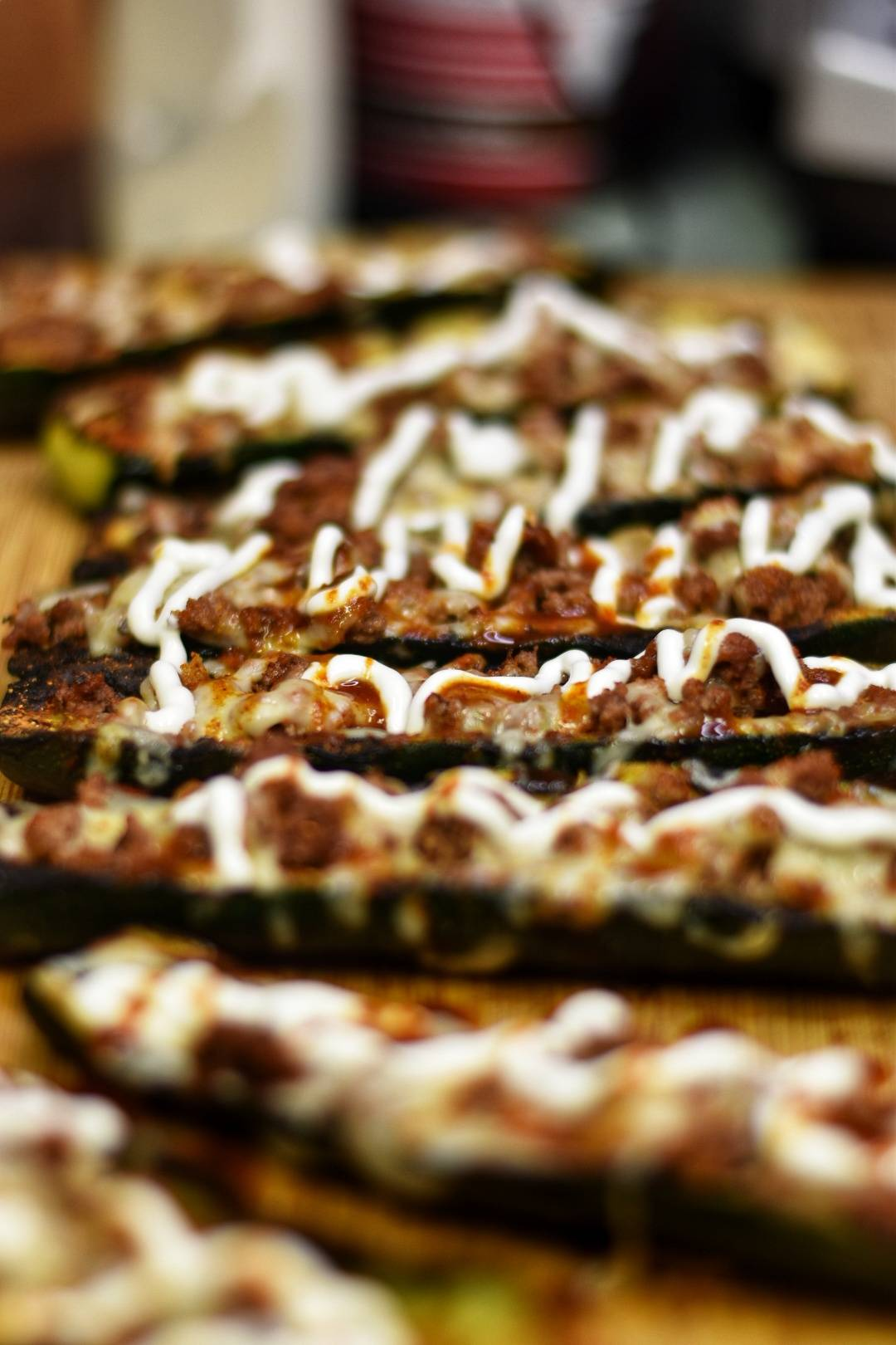 Grilled zucchini with ground beef and shredded cheese topped with sour cream and chili sauce