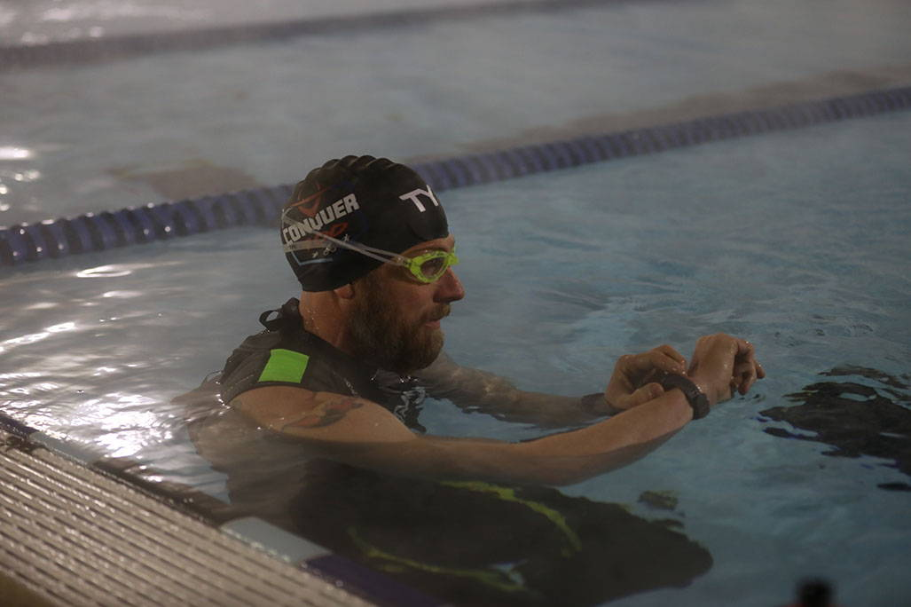 James Lawrence looking at watch in pool