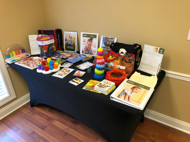 table with infant and toddler books, toys, and equipment