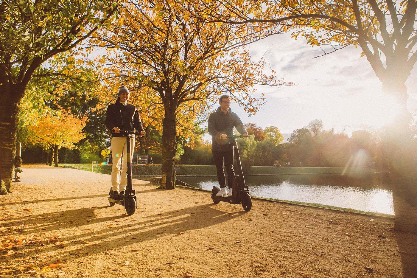 okai-es200-escooter-couple-riding-scooters-autumn-path