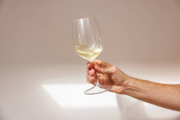 A white wine glass portraying the the importance of it to be smaller to maintain chill.