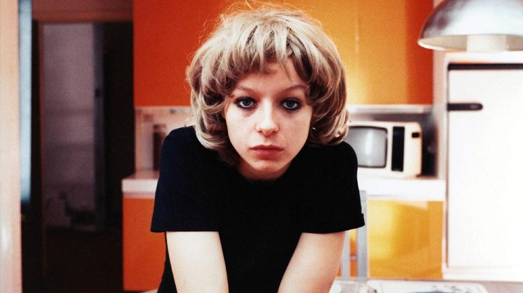 A young woman in a kitchen staring straight ahead
