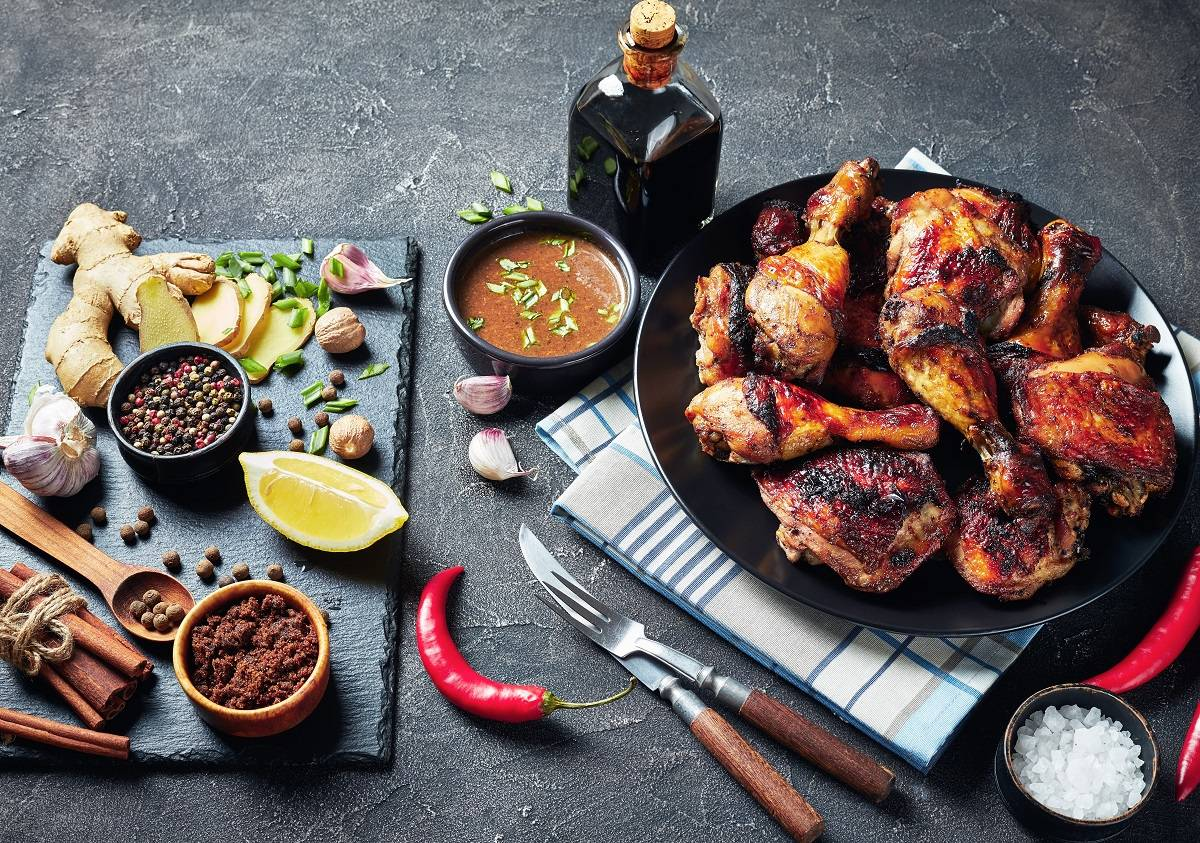A flat lay of jerk chicken pieces and the herbs and spices used to make the marinade - jerk chicken is the national food of Jamaica