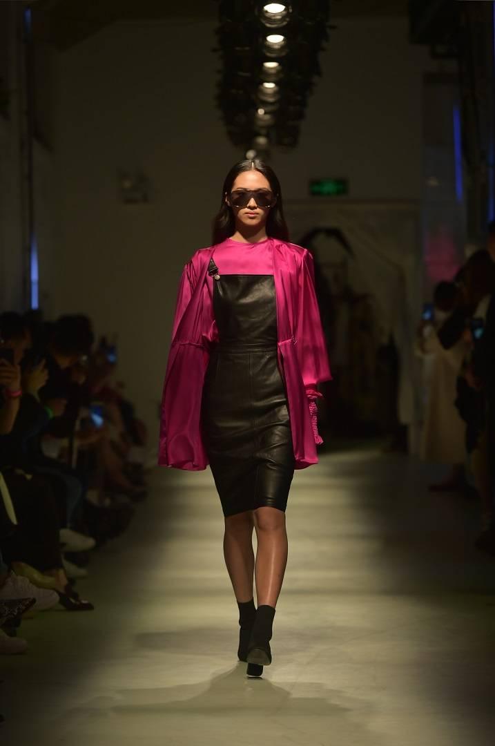 Robe en cuir noir à bretelles avec blouse en satin de soie fuchsia
