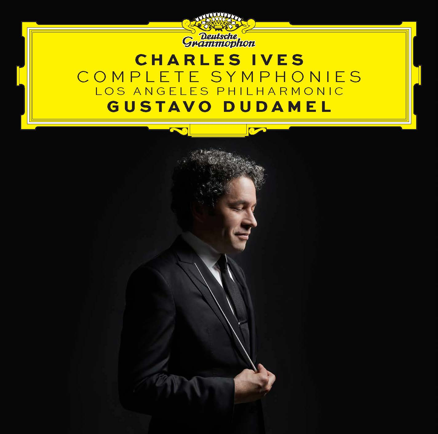 """Album cover for Ives: Complete Symphonies recording. Side profile of Gustavo Dudamel against a black background looking down, smiling, holding his baton. Above his head, """"Charles Ives, Complete Symphonies, Los Angeles Philharmonic, Gustavo Dudamel"""" in a yellow Deutsche Grammophon text box."""