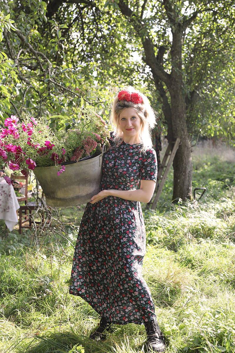Kitten Grayson in YOLKE's Juniper Dress holding a tub of flowers in a field