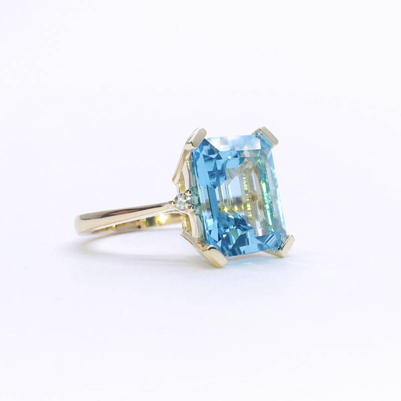 Yellow gold ring replicating Princess Diana's ring with blue topaz