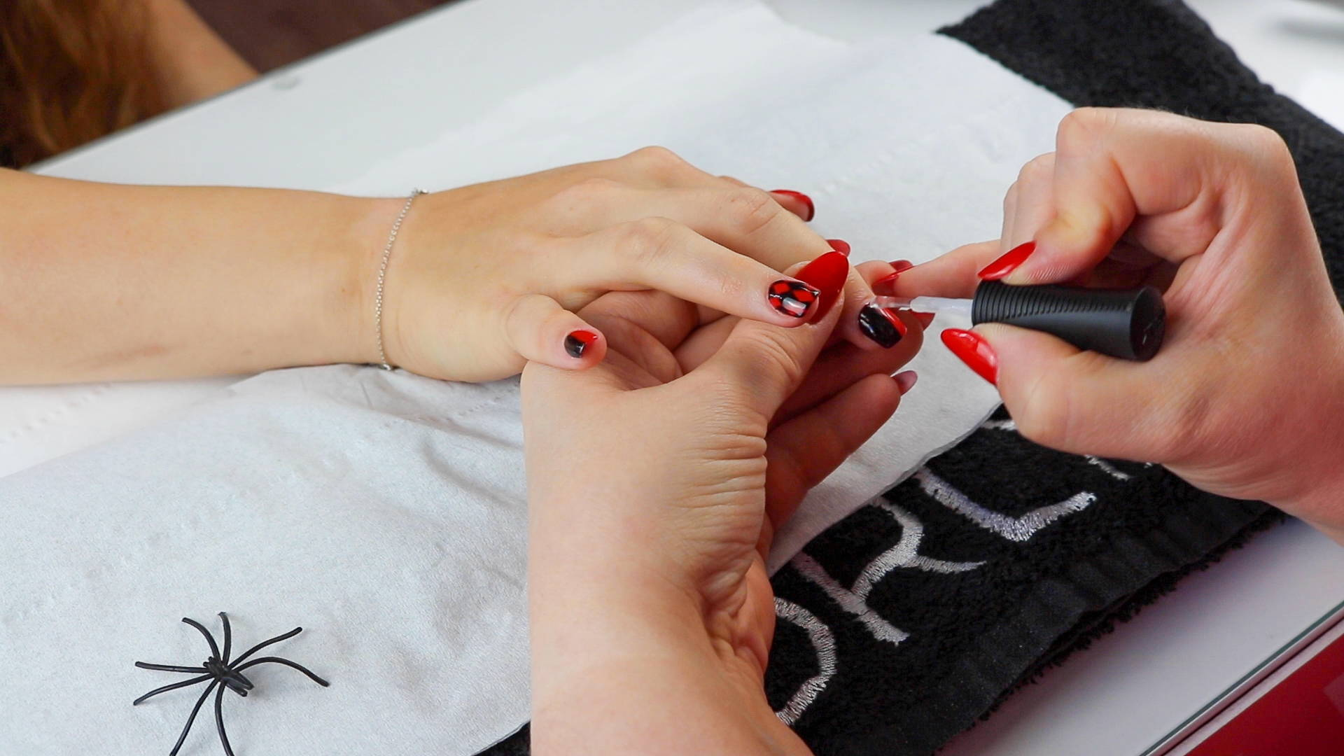ORLY Glosser Topcoat being painted over Harley Quinn nails