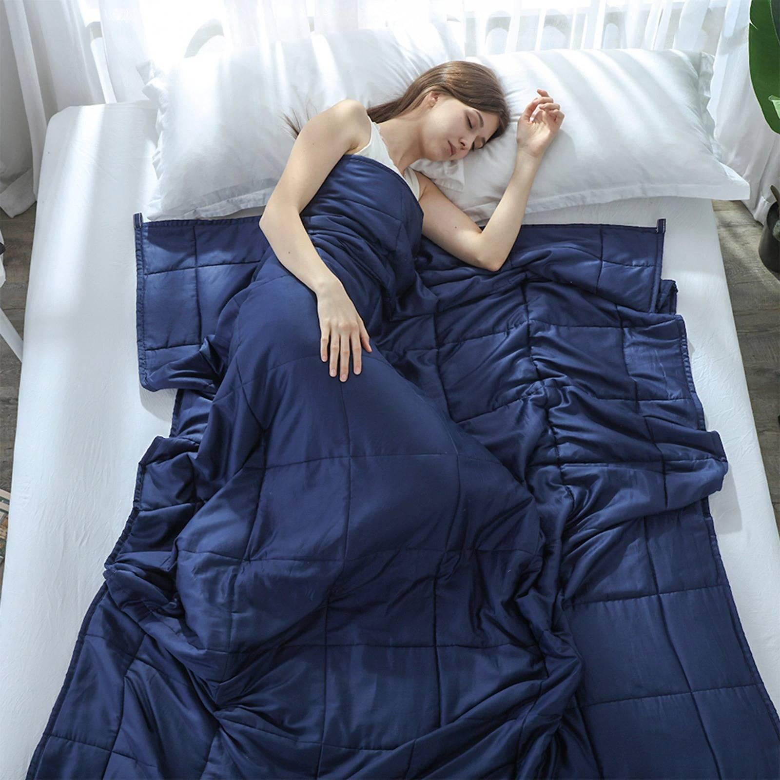 Femme utilisant une couverture lestée dans un lit