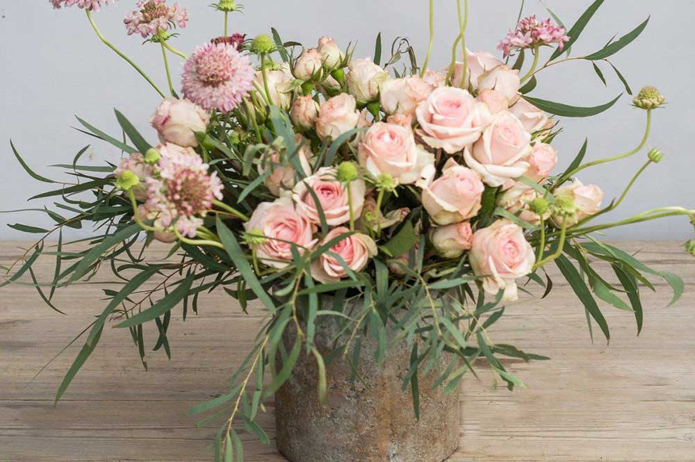 Bouquet of pink roses and greenery in a wooden vase