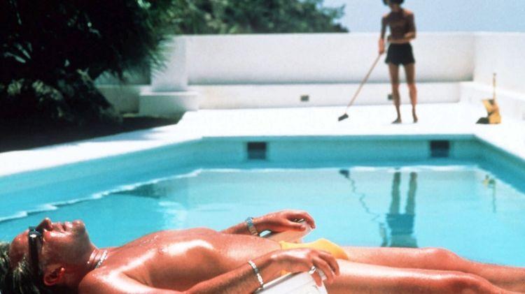 A man sunbathing beside a swimming pool