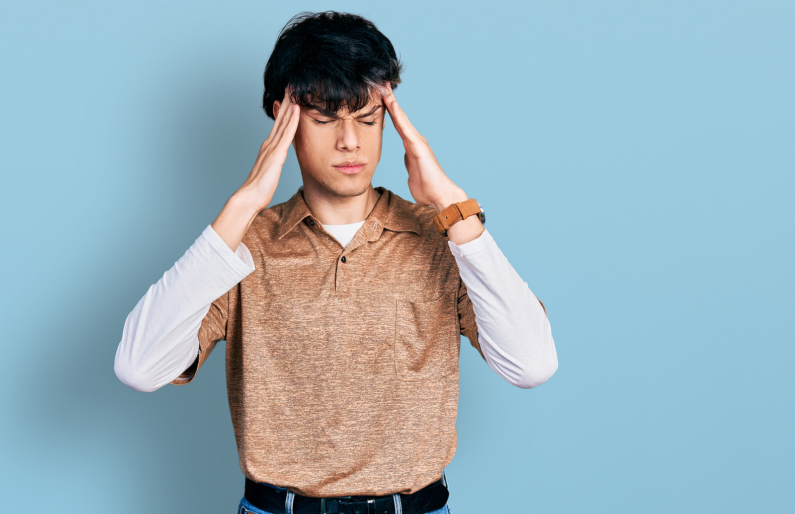mage of a young hipster guy wearing 90s long sleeve shirt and collar shirt, with his hands on his head looking frustrated.