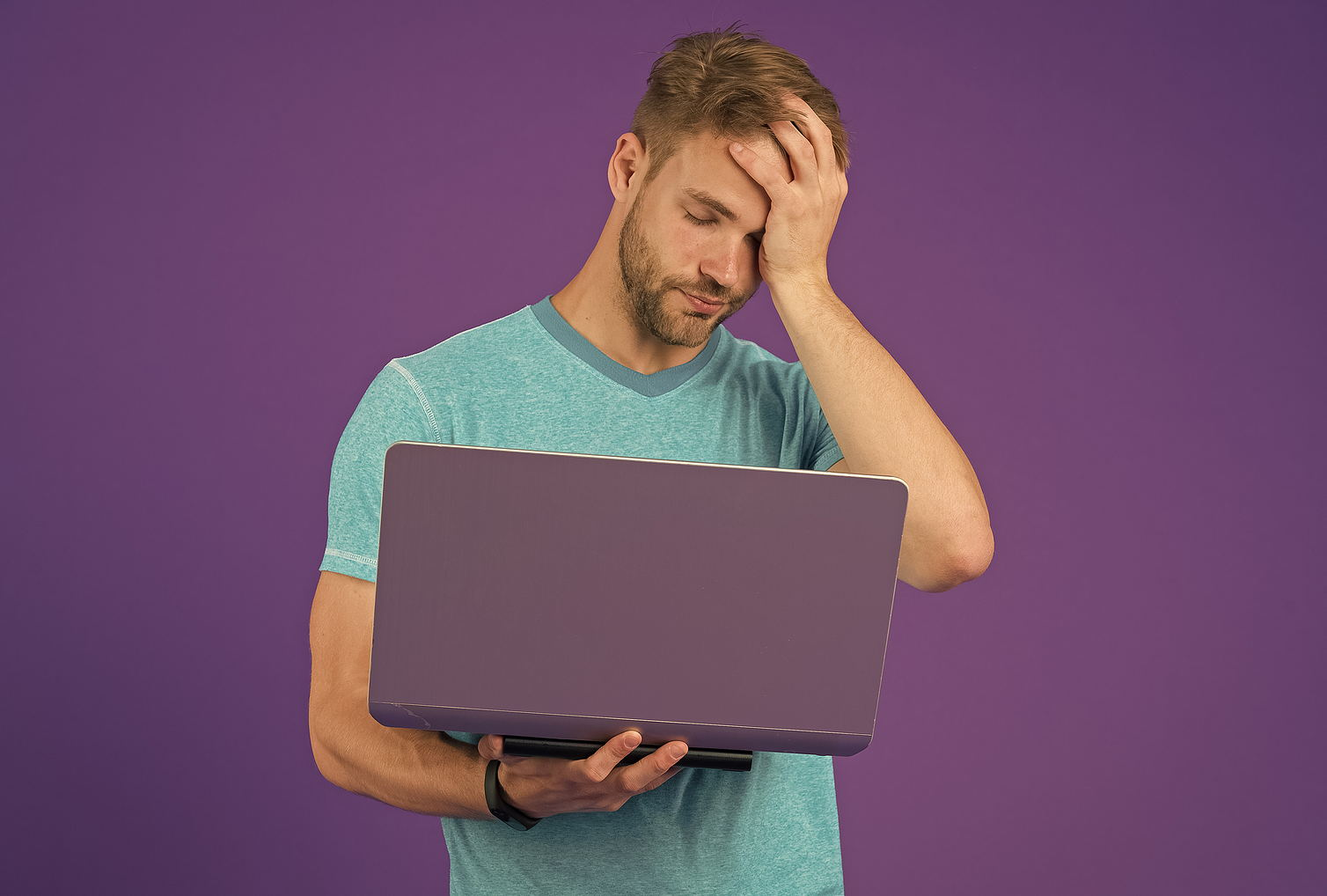 A tired man holds his computer in one hand and his head in the other worried against a purple background.