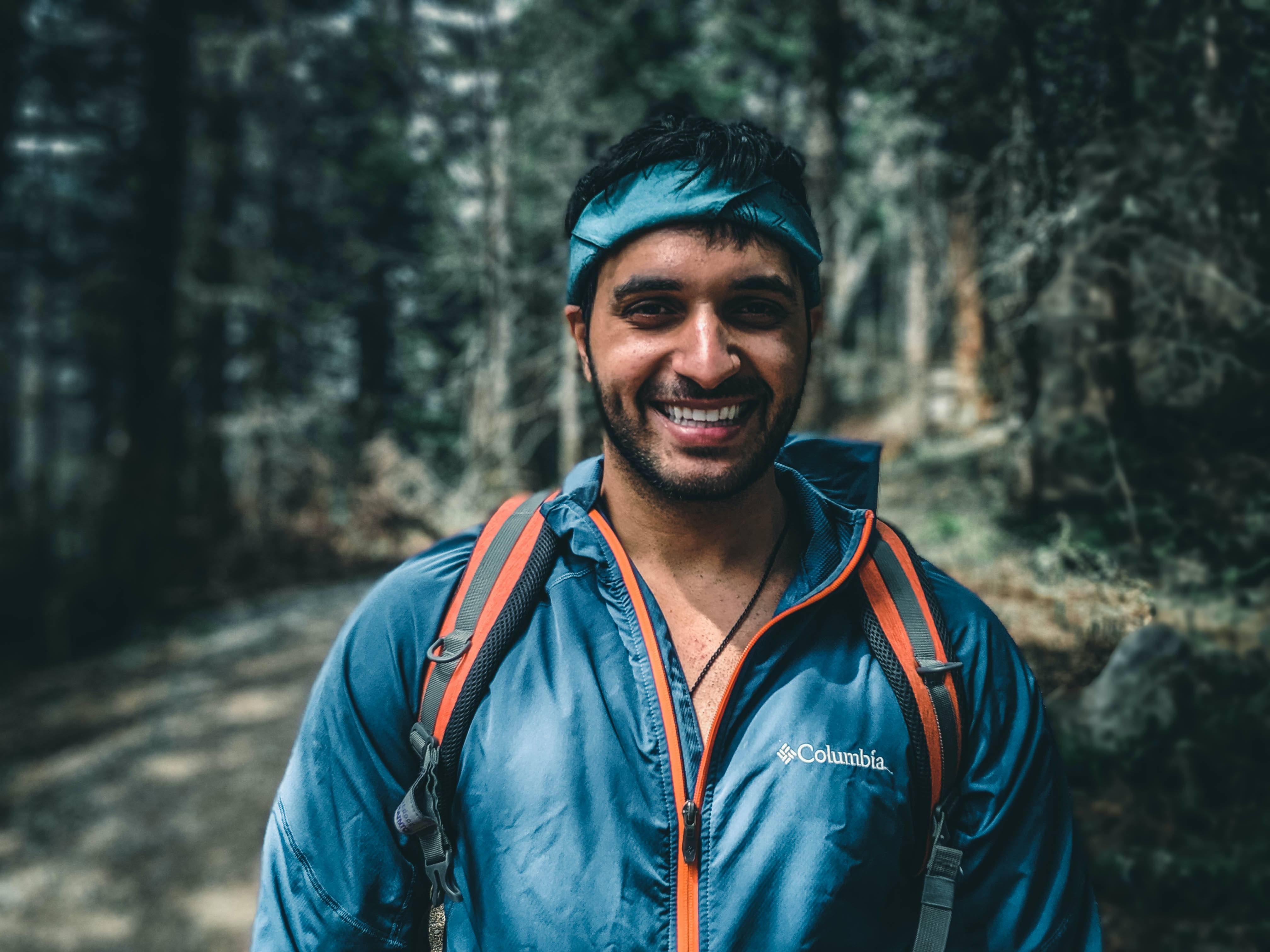 An attractive Indian man wearing a windbreaker and a bandana. He is smiling and on a wooded path hiking.