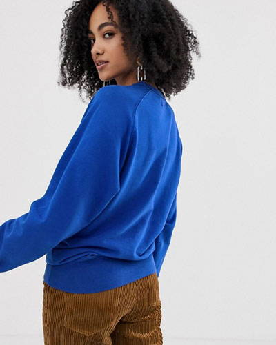 Back of woman wearing bright blue organic cotton sweatshirt from sustainable clothing brand Kings Of Indigo