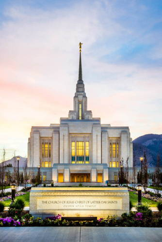 Vertical photo of the Ogden Temple and sign at sunrise.