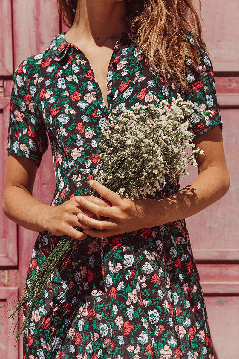 Women in YOLKE Juniper Dres featuring florals on a dark background holding a bouquet of flowers