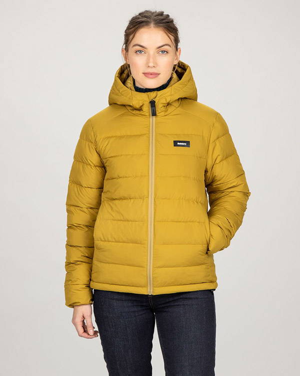Woman wearing recycled polyester insulated winter jacket in yellow from Finisterre