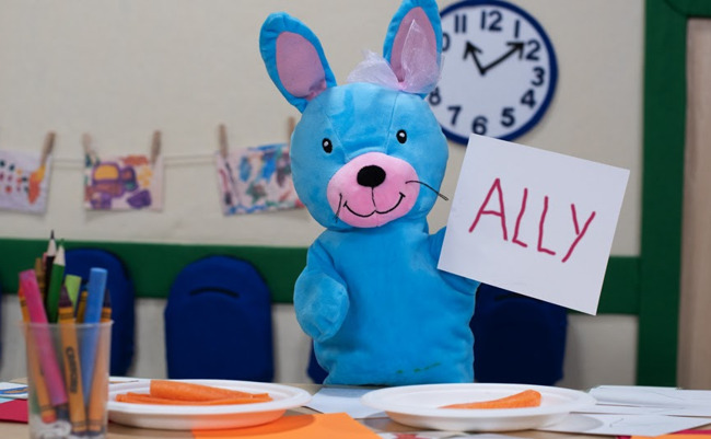 Primrose Friend Ally the bunny holding a paper with her name on it at the lunch table