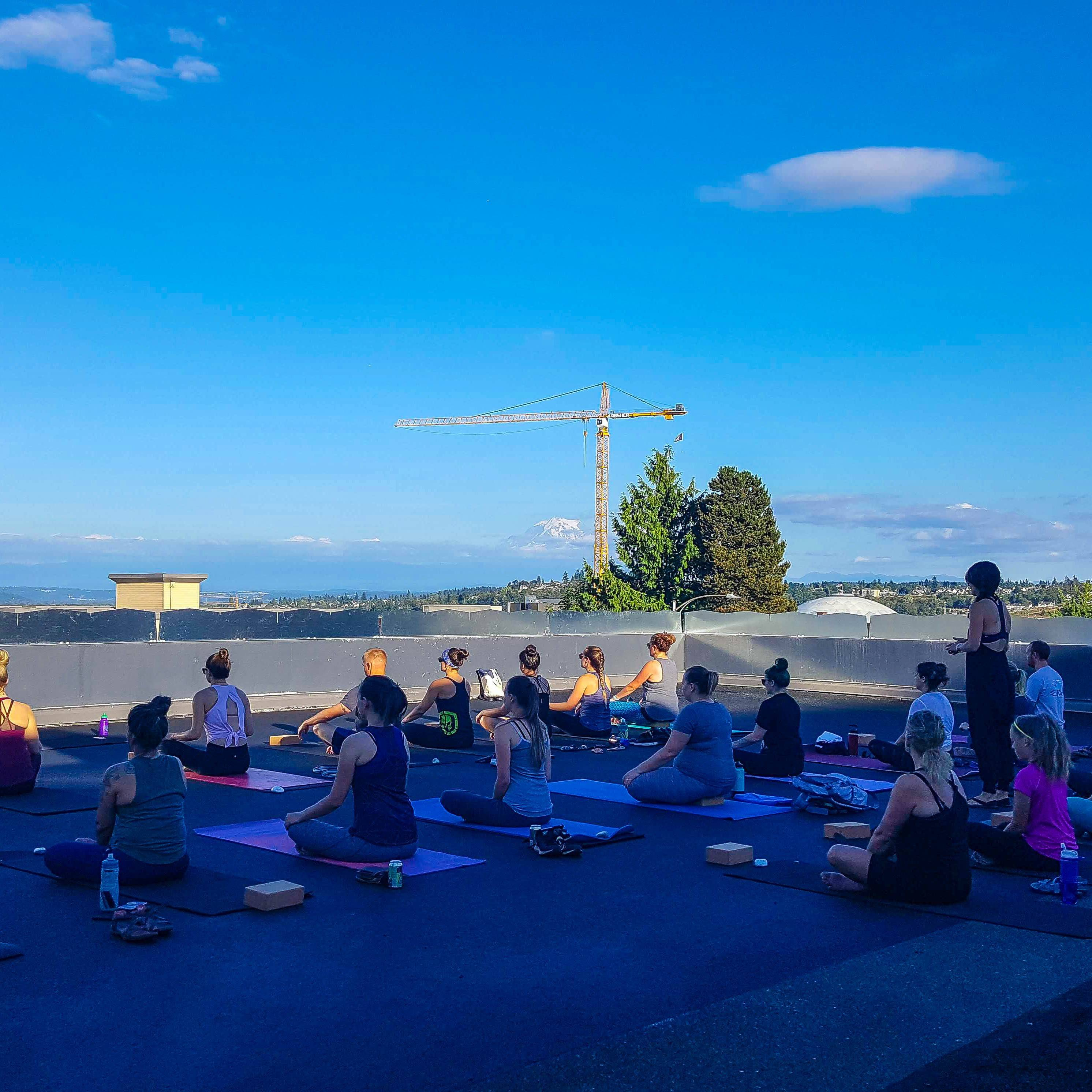 Yoga on a rooftop with blue skies and a view of Mt. Rainier.