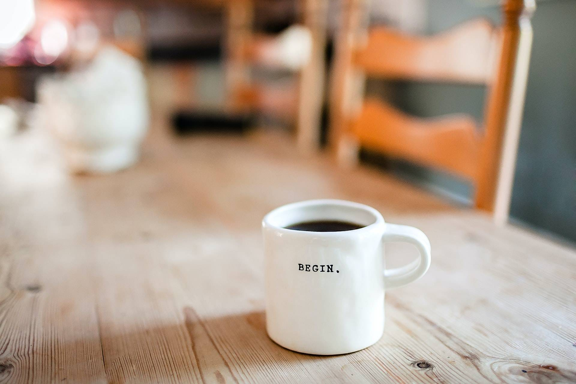 """A coffee mug on a table with the word """"begin"""" written on"""