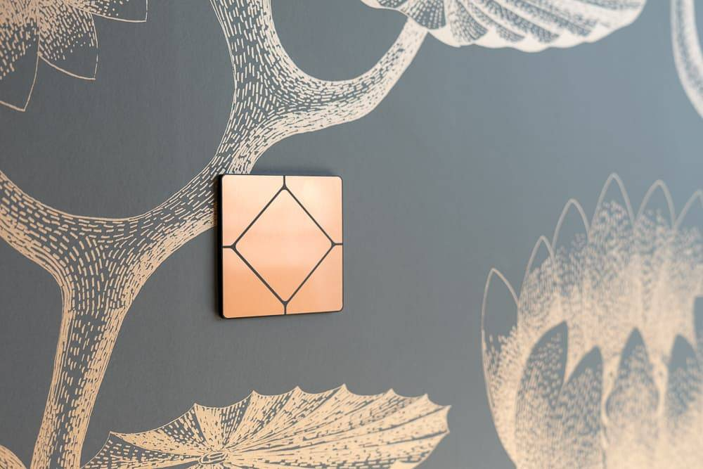 Faradite TAP 5 brushed copper smart home switch plate on decorative wall