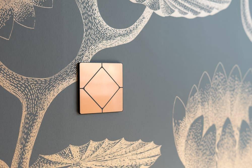 Faradite TAP 5 Smart-Home-Schalterplatte aus gebürstetem Kupfer auf dekorativer Wand