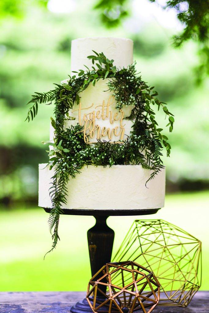 Three tiered white wedding cake with a wreath decoration in the center