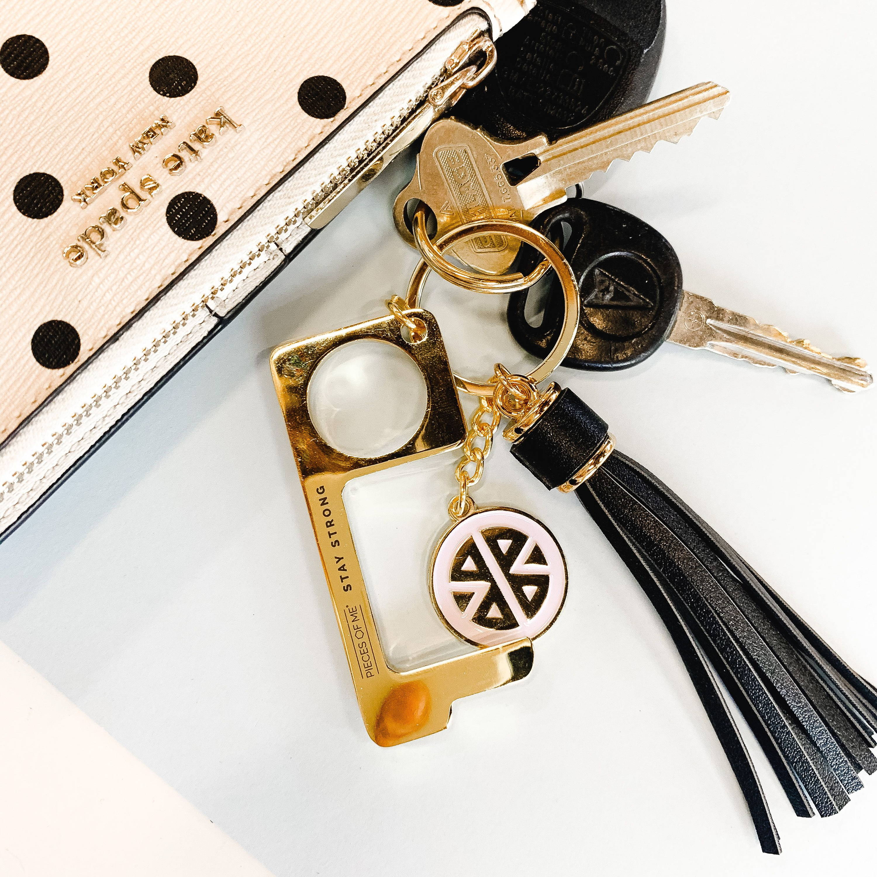 Gold no-touch tool with black tassel