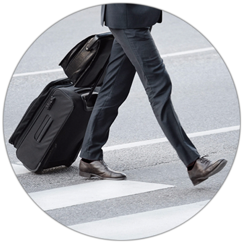 A man walking across the street in business attire dragging suitcases behind him