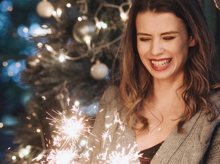 girl with brown hair smiling while looking at sparkler