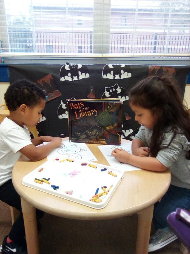 A boy and girl drawing at a small wooden table with a book about bats in between them