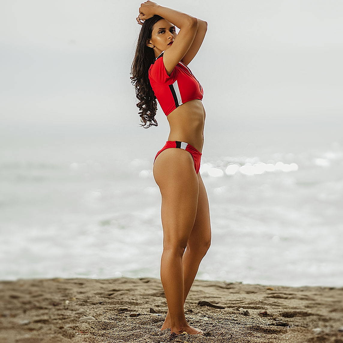 Desi girl in a red sporty 2 piece bikini on the beach