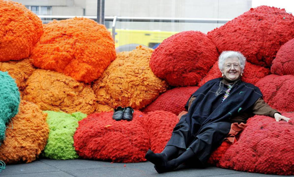 Sheila Hicks lying on an instillation of red woven material.
