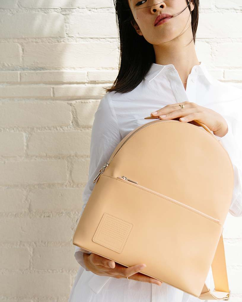 A woman in white shirt presenting a beige Opus Mind bagpack