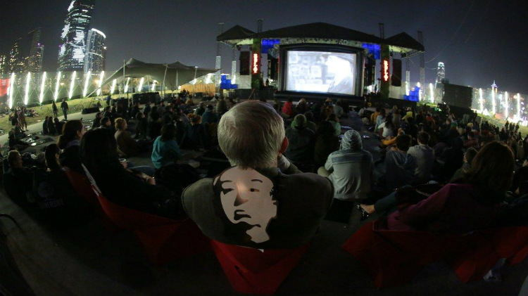 An audience watching a film screening with a man wearing a Hitchcock mask
