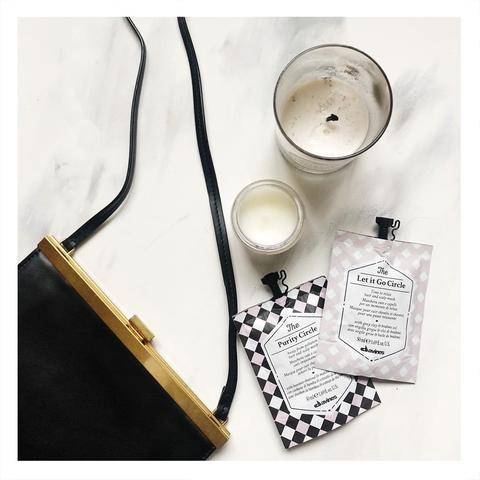photo of Davines products on a table with a purse and candles