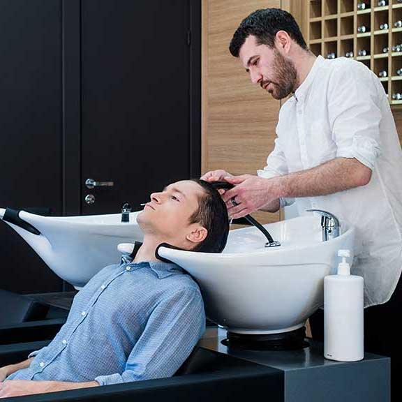 stylist washing man's hair