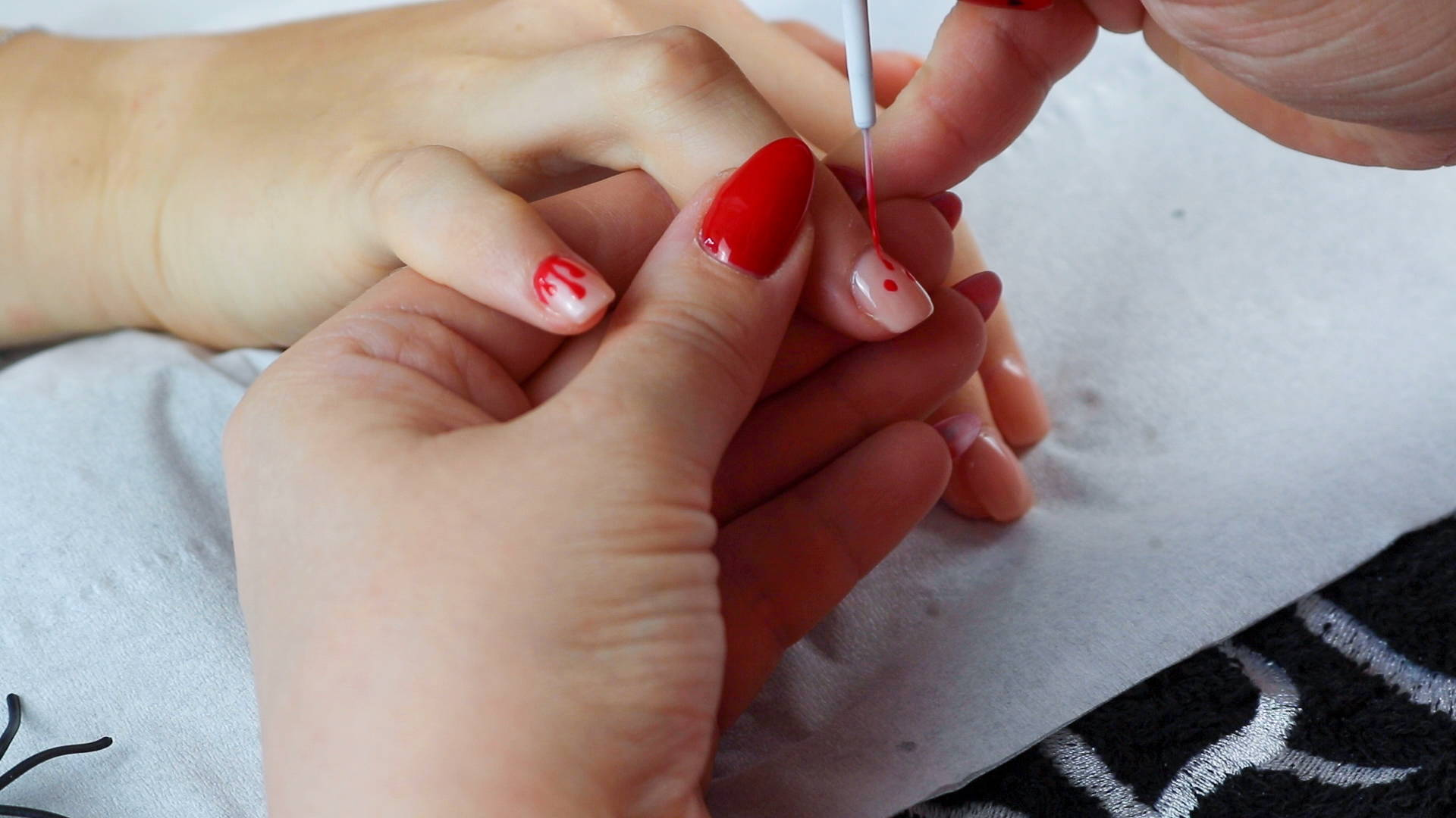 Blood nails detail being added to a nail using a striping brush and ORLY Haute Red
