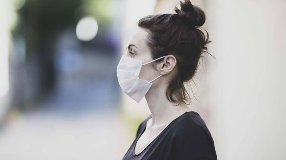 Une femme qui se protège de la pollution atmosphérique avec un masque