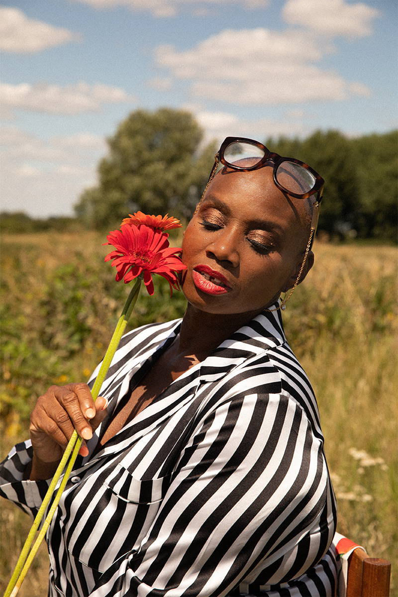 Andi Oliver wearing YOLKE holding a flower in a field