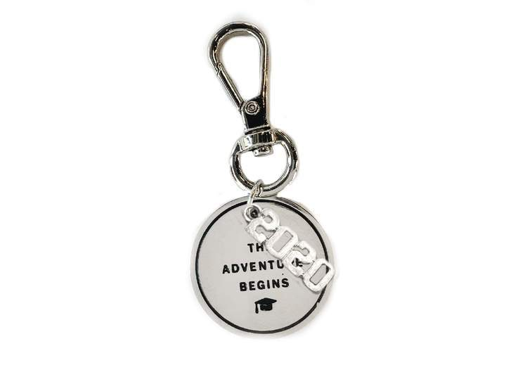 "Circular keychain charm engraved with ""The Adventure Begins"" in silver"