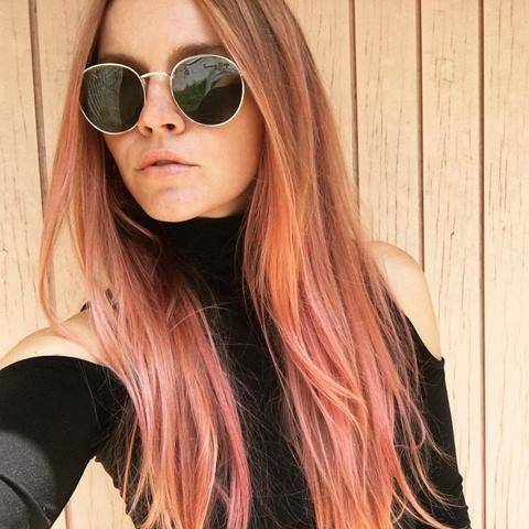 woman with long pink hair and sunglasses