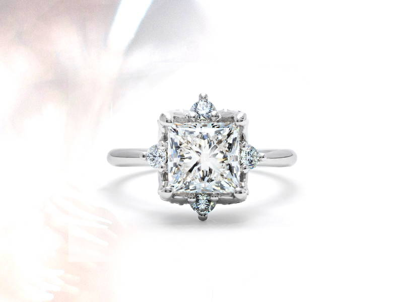 High jewellery ring in white gold with a princess diamond in the centre and four small diamonds around it.