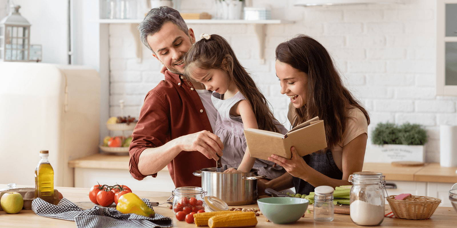 Father, mother, and daughter playfully cooking together.