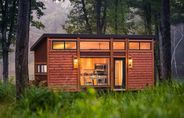 a tiny home is nestled away in the forest, oh how serene