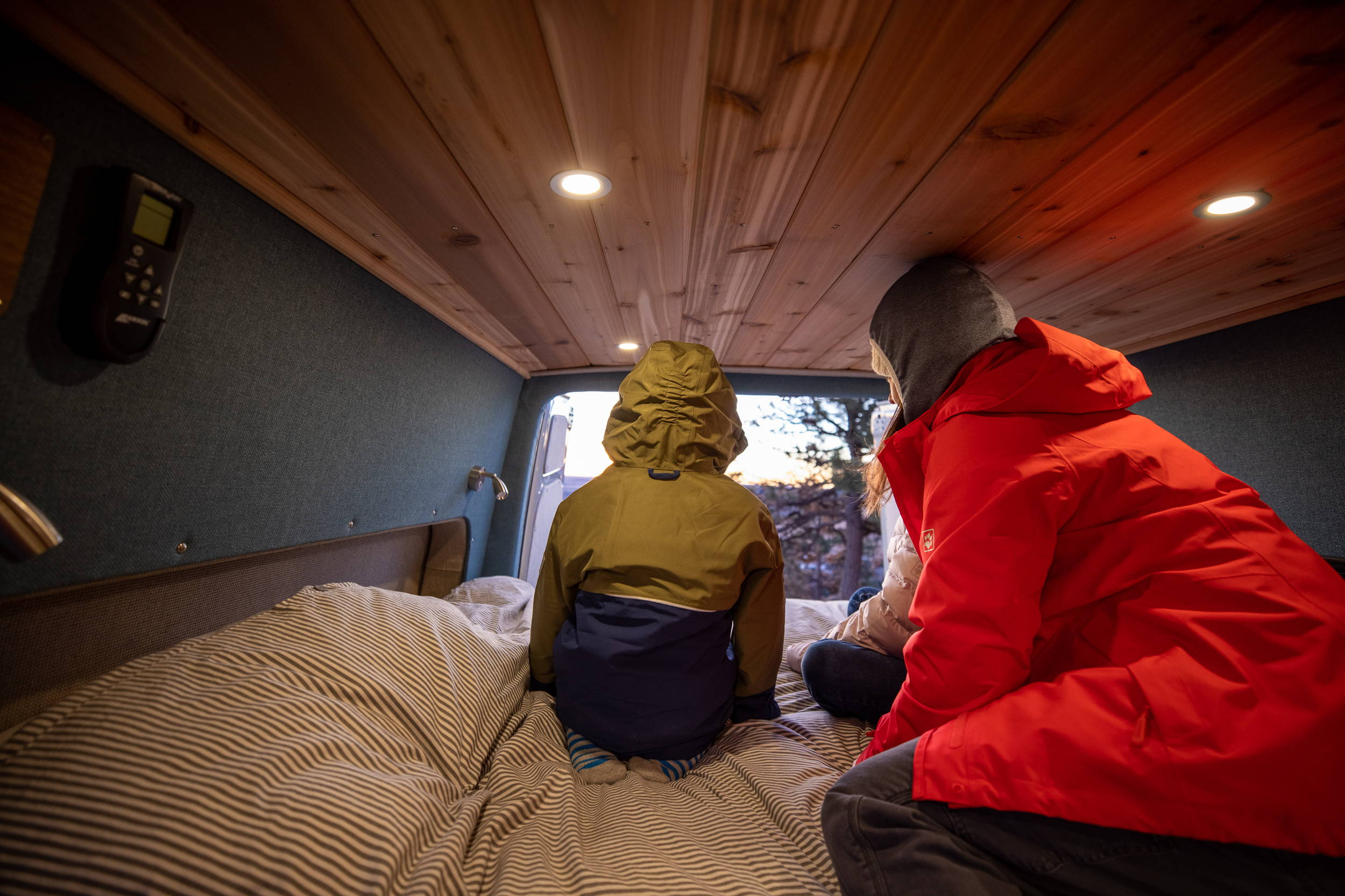 Rack & Roll - Sprinter 144 Van Conversion - Woman and Children Enjoy View from Lofted Bed - The Vansmith